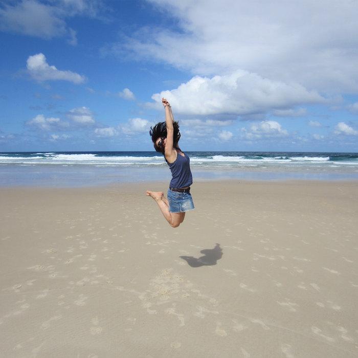 Sprachreisen für junge Erwachsene Frau am Strand spring in die Luft