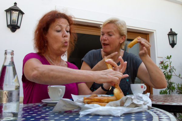 Zwei 50 plus Frauen essen Churros