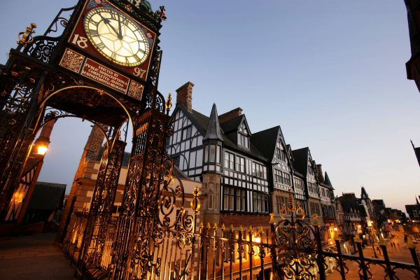 City of Chester, England. Commissioned by public subscription to celebrate Queen Victoria's Diamond Jubilee, the John Douglas designed Eastgate Clock sits on top of Chester City Wall at Eastgate Street. Night view of the clock with the Chester Grosvenor and Spa 5 star hotel in the background.