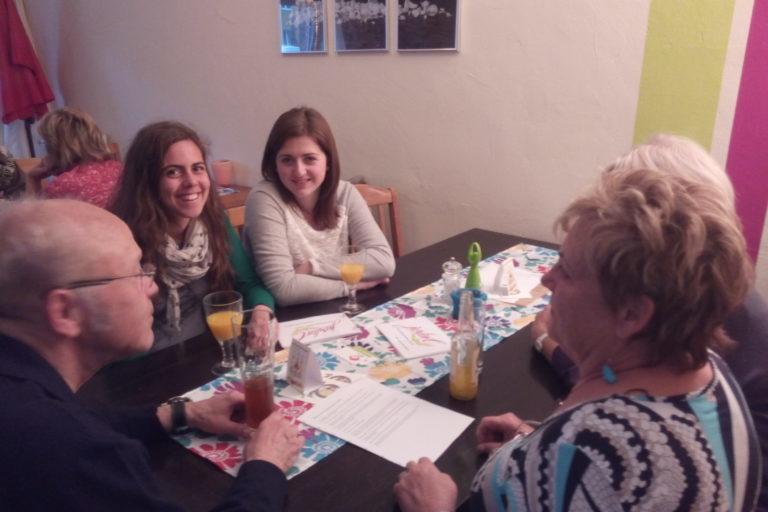 Alt und jung trifft diskutiert am Tisch beim Café des Langues in Berlin.