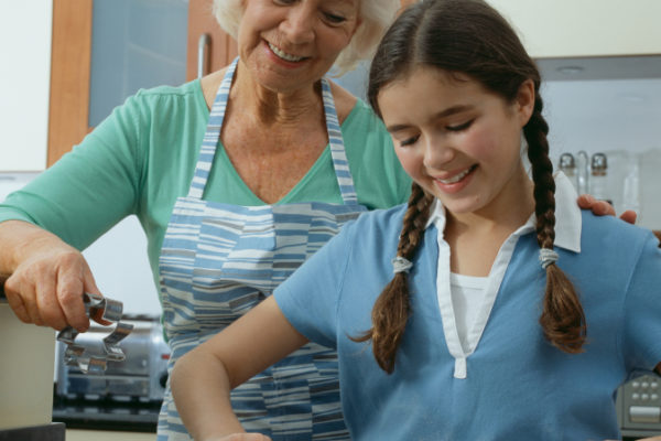 Girl (10-12 years) learning to make pastry, watched by her grandmother