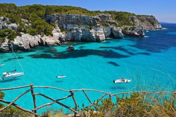 Boote in kristallblauem Wasser an der Küste von Menorca